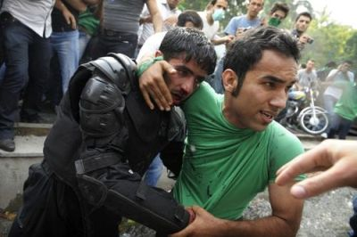 A demonstrator rescues a beleaguered riot policeman, Iran, 13 June 2009