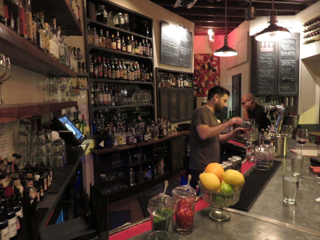 Photograph of the interior of a bar. Glassware and gruit line the far edge of the bar. A bartender is pouring a drink a few seats down. In the background is large dark shelf full is liquor bottles.